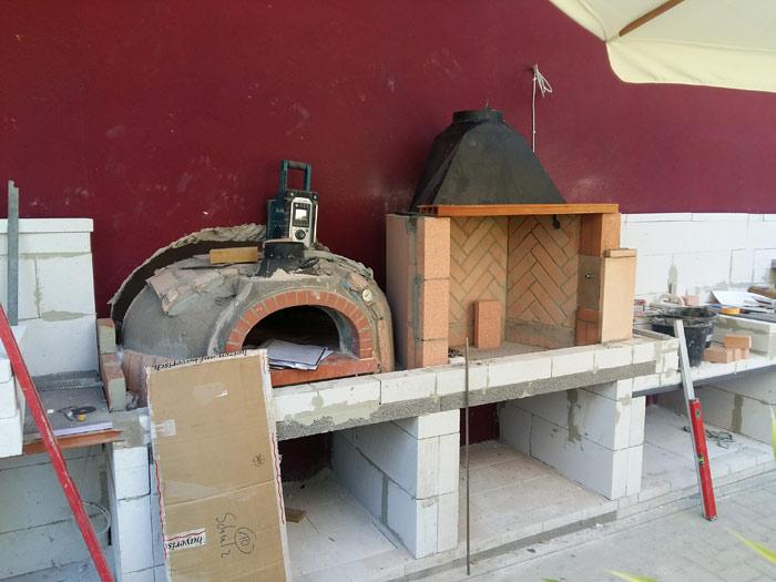 Brot- und Pizzabackofen neben offenem Grill